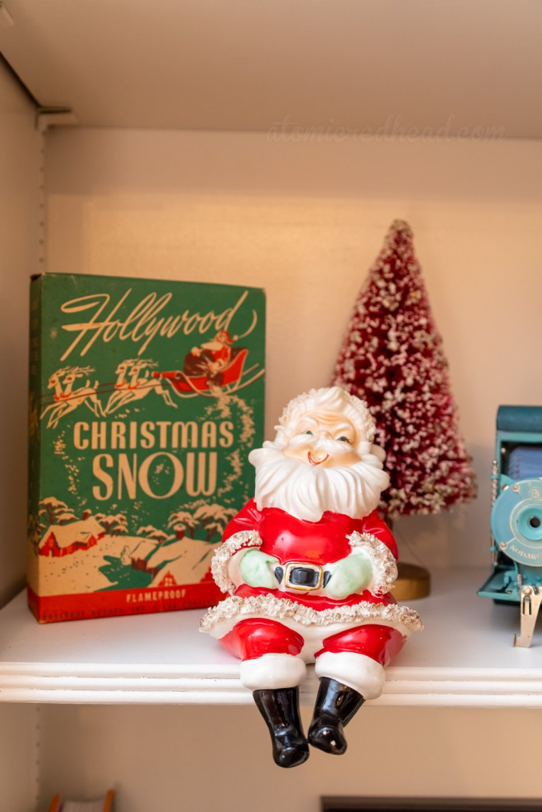 "A ceramic Santa sits on a self, with a box of ""Hollywood Christmas Snow"" behind him."