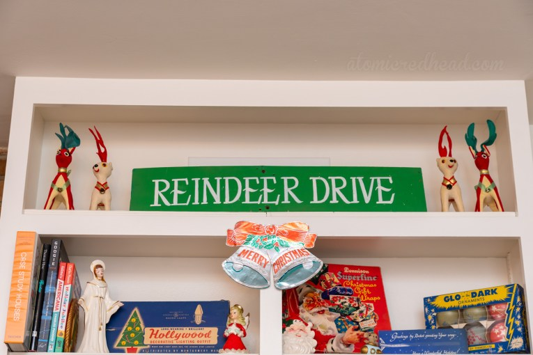 "A sign reads ""Reindeer Drive"" and is flanked by four small stuffed reindeer."