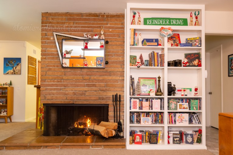 Overall view of our fireplace with a built in bookshelf on the right. Above the fireplace is a modern, abstract shadow box with various ceramic Christmas figures.