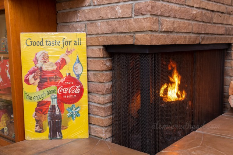 Close-up of our fireplace, and a poster featuring Santa selling Coca-Cola.