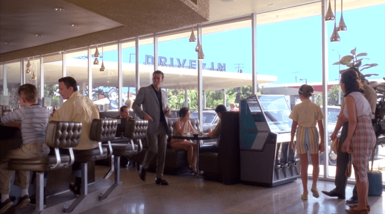 "Screencap from Mad Men: Don, in grey slacks and jacket, and black shirt, walks into Bob's. A jukebox is near the window, ""Drive-In"" is visible outside through the window."