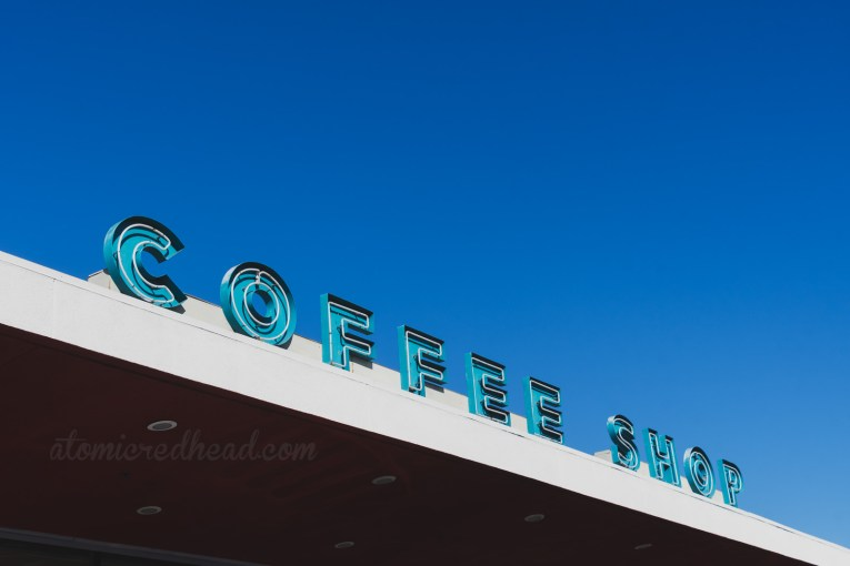"""Coffee Shop"" spelled out in blue neon."