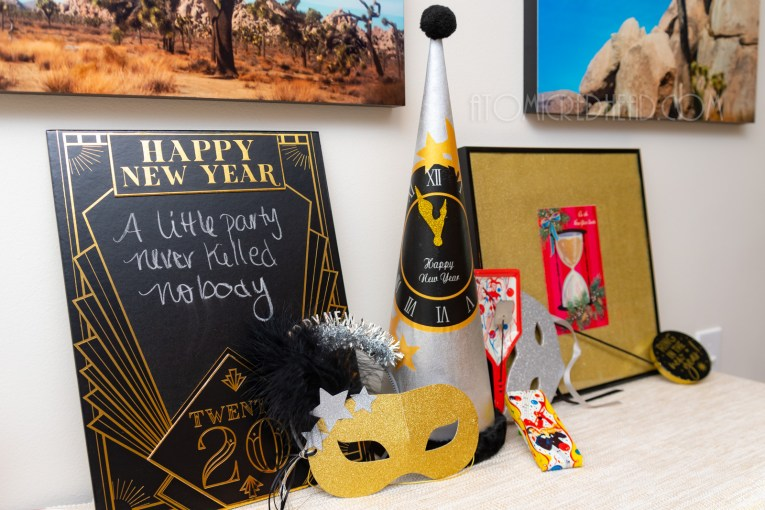 Close-up of a silver hat with a black and gold clock, a gold glitter mask, and variety of vintage noise makers.