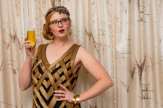 Myself, wearing a black and gold chevron patterned beaded flatter dress, with a black and gold headband.