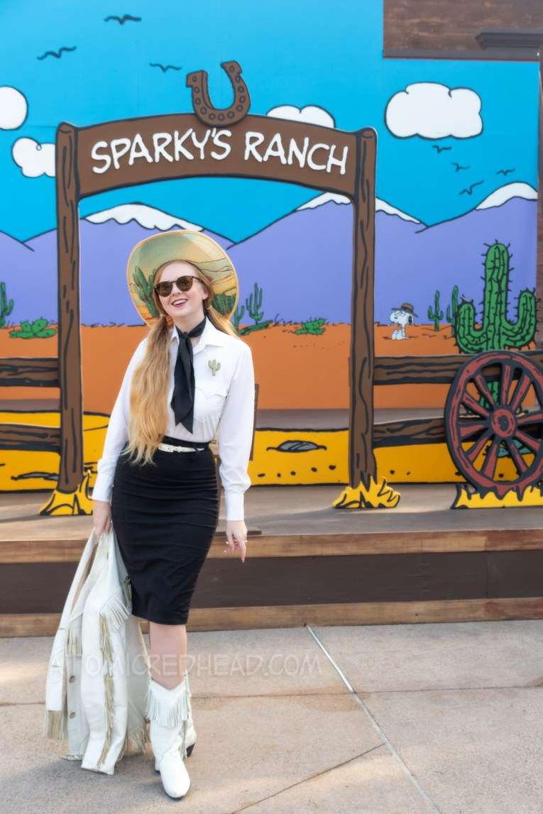 Myself standing in front of a western backdrop done in the style of Peanuts creator Charles M. Schulz. I'm wearing a cowboy hat with a cactus print on the brim, a white fringe leather jacket, a white western wear shirt, a black scarf, black skirt, and white fringe leather boots.