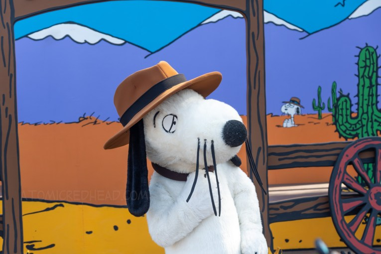 Spike stands in front of the western backdrop. He is a black and white beagle like Snoopy, but thinner, with dropping whiskers and a brown hat.