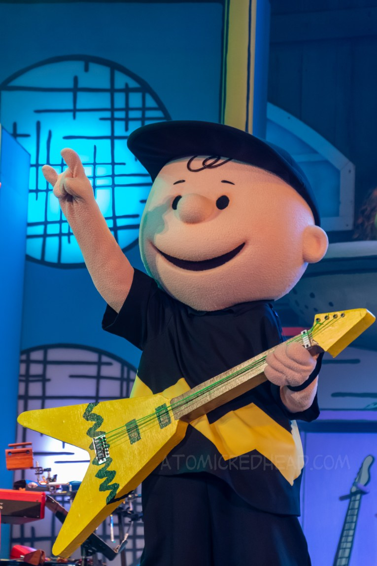 Charlie Brown rocks out at Woodstock's Music Festival, with a guitar featuring his iconic yellow with black zig-zag design.