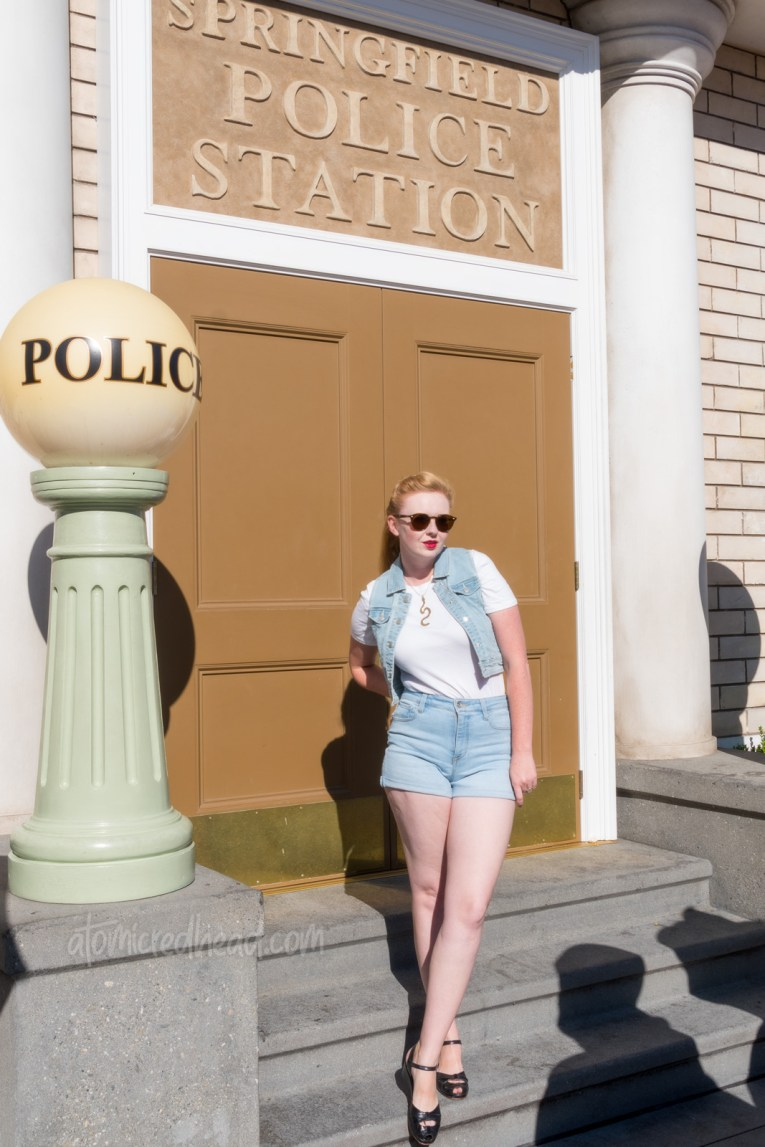 Myself, wearing a white t-shirt, with a jean vest over, and jean shorts, standing in front of Springfield Police