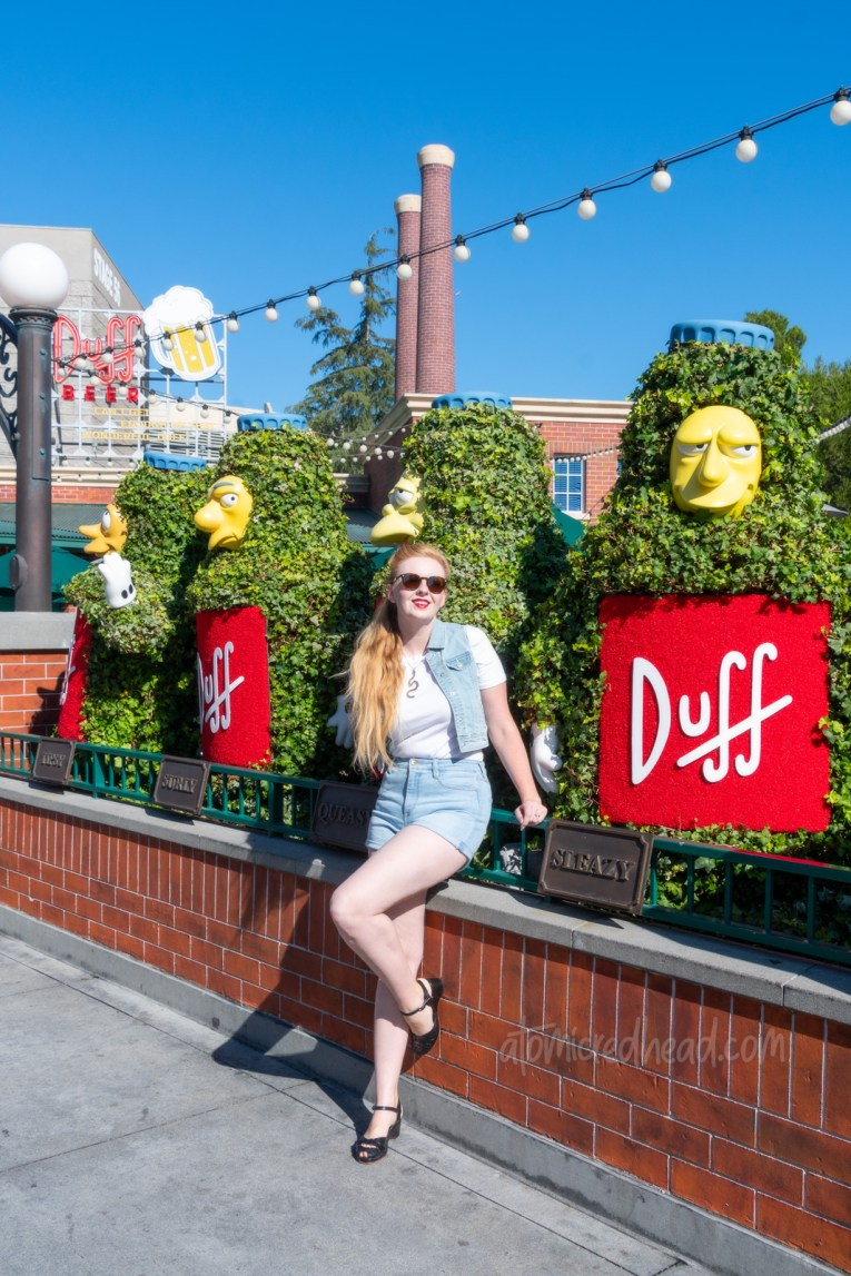 Myself, wearing a white t-shirt, with a jean vest over, and jean shorts, standing in front of topiaries of Duff beer bottles.