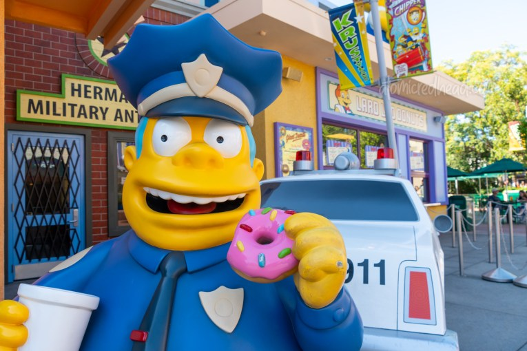 Statue of Chief Wiggum standing in front of his crashed police car, eating a donut.
