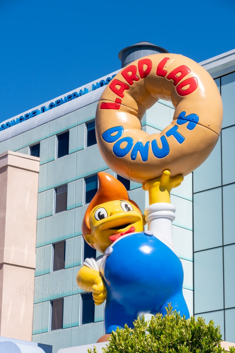 Statue atop Lard Lad Donuts, of a kid in overalls with cowlick hair holding a giant donut.