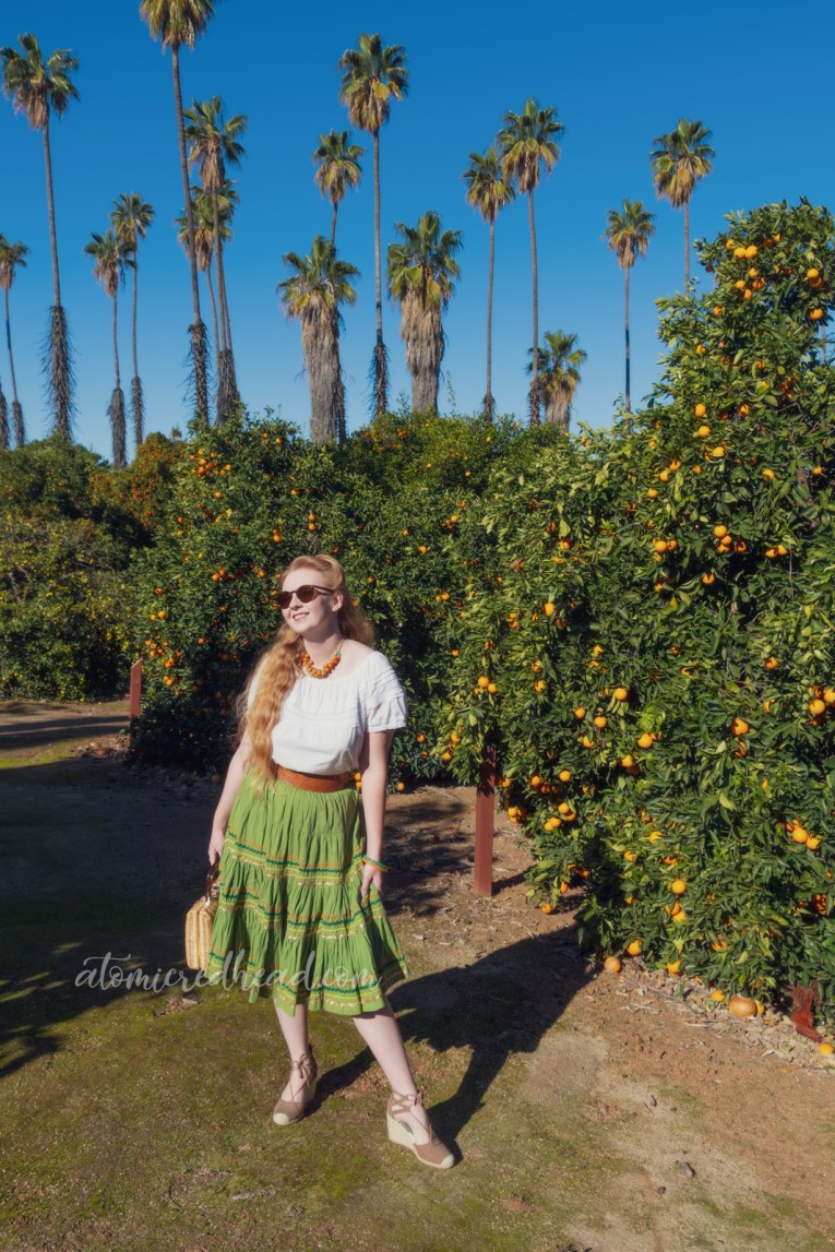 Myself, wearing a necklace of Bakelite oranges and leaves, a white peasant top, and a green skirt with orange, gold, and dark green rick-rack, standing among orange trees.