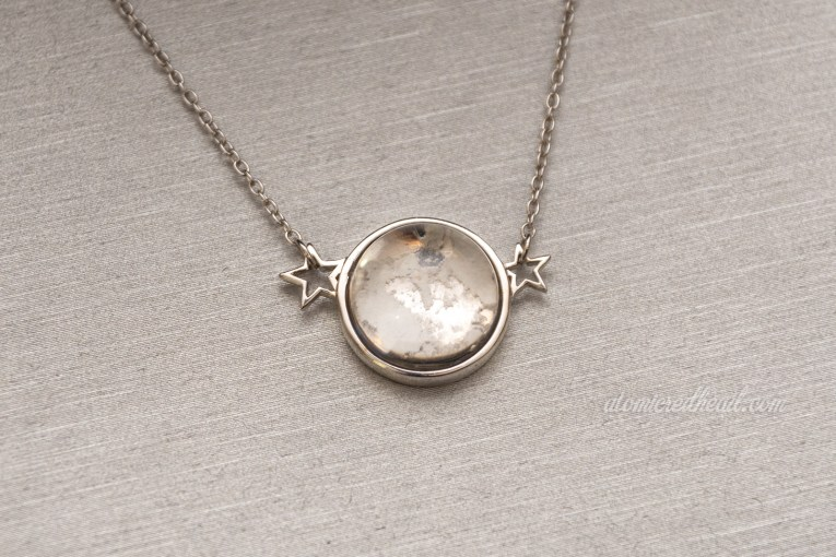 Close-up of the Once a Moon necklace. A circular pendant flanked by two silver stars. The circular portion features a clear glass cabochon with lunar dust underneath.