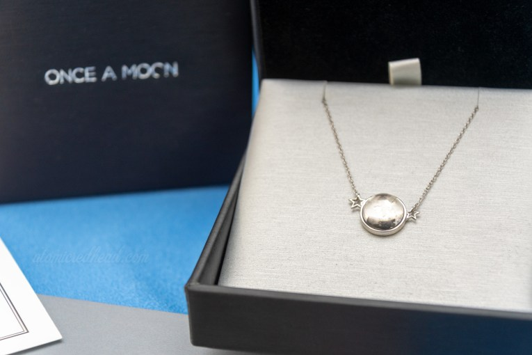 Once a Moon necklace in packaging. A small circular moon line pendant flanked by two small silver stars sits in a silver and black box.