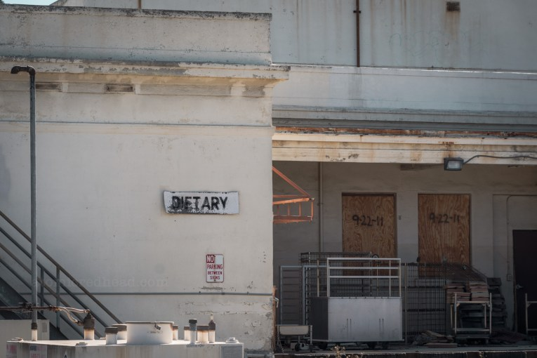 "The docking bay of an industrial building. The doorways are boarded up. On the dock sits carts with food trays. A white sign reads ""Dietary"""
