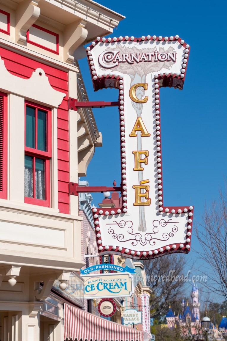 "The sign for the Carnation Cafe, which has a large carnation flower on it and reads ""Carnation Cafe"" in gold letters. The building itself is red with white trim."