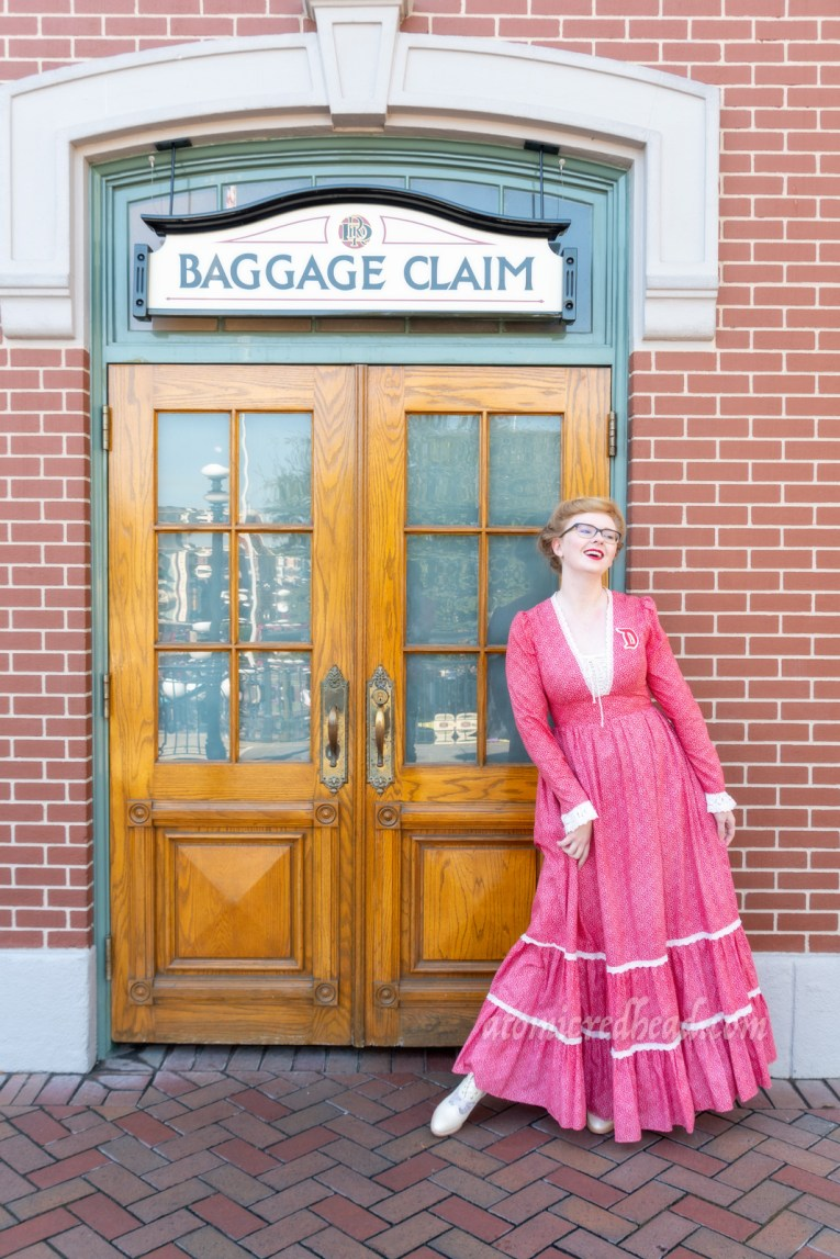 "Myself, standing in front of the Main Street Train Station, wearing a long, red dress with a small floral pattern, with lace trim at the laced V-neckline, and cuffs. A red ""D"" brooch edged in white is worn on my left shoulder, my hair in a Gibson Girl updo."