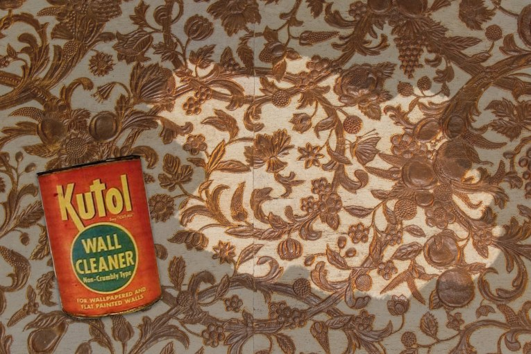 A white and gold wallpaper is marred by black soot, a small patch has been wiped away to make it clean. A red and green can of Kutol Wall Cleaner sits in the lower left croner.