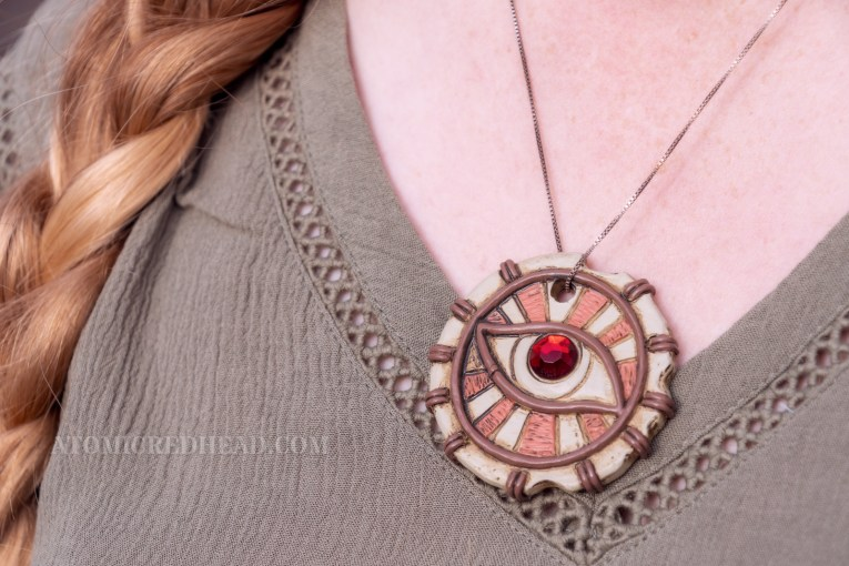 "Close-up of my necklace, ""The Eye of Mara,"" a circular pendant with an eye with a ruby as the center, with rays radiating out from it."