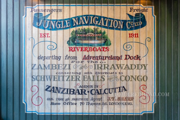 "A large, hand-painted mural with a riverboat, reads ""Jungle Navigation Co. Ltd. Est. 1911. Passengers Freight. Riverboats departing from Adventureland Dock for the...Zambezi and Irrawaddy connecting with Riverboats to Schweitzer Falls and the Congo. Agents in Zanzibar - Calcutta. Gen. Trav. and Passenger Agent J.T. Sharp. Home Office 70 Thames Rd. London Eng."""