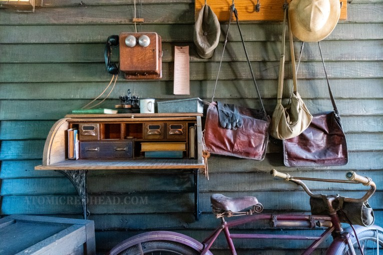 A wall mounted roll top desk holds mail and books. Above it an old phone. A coat rack is above and to the right, from it hangs hats and bags. Below is an old bicycle.