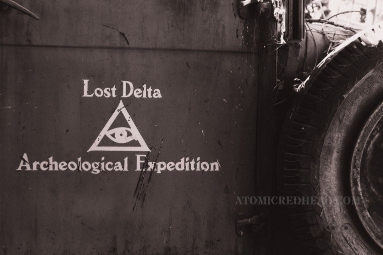 "The door of a cargo truck reads ""Lost Delta Archeological Expedition"" and features a triangle with an eye in the center."