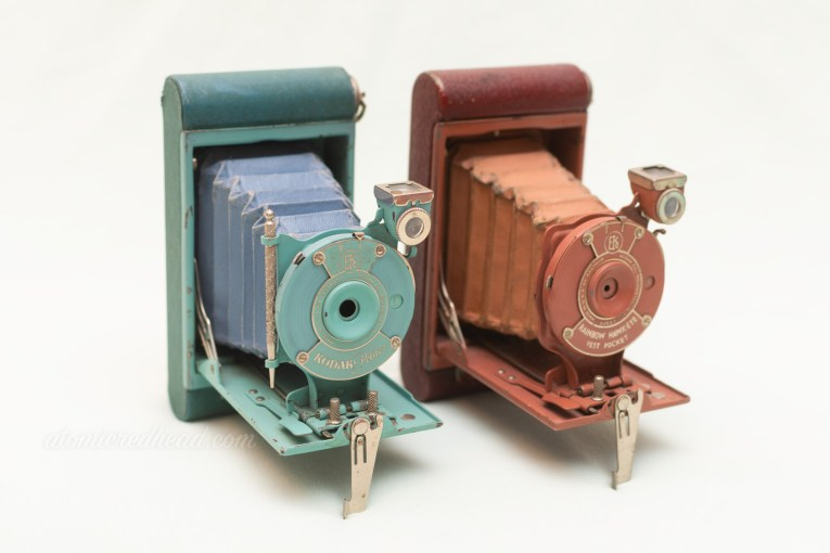 Two small cameras. Each feature a bellows. The camera on the left is teal blue in color, and is the Kodak Petite, the one on the right is a dusty rose, and is the Kodak Rainbow Hawkeye.