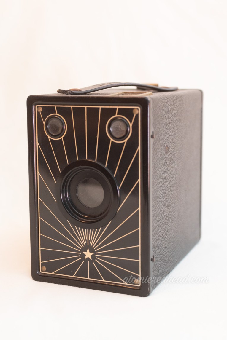 Macy M-16. A black box camera, with a metal front plate that features a small star at the bottom with radiating lines.