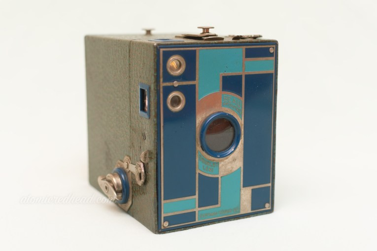 Kodak Beau Brownie. A box camera that is blue, with a metal plate on front with a geometric two-tone blue deco design.