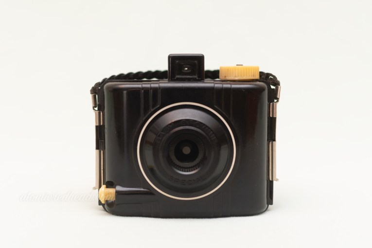 Kodak Baby Brownie Special. A small, black square camera made of bakelite. Lens is circled with white.
