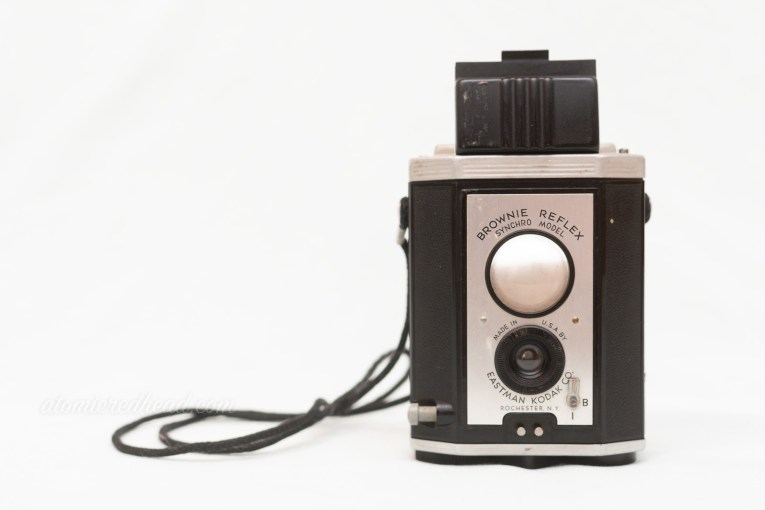 Kodak Brownie Reflex Synchro Model. A silver and black dual lens.