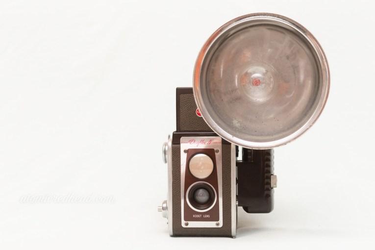 Kodak Duaflex IV. A brown and silver dual lens camera with a flash attachment.