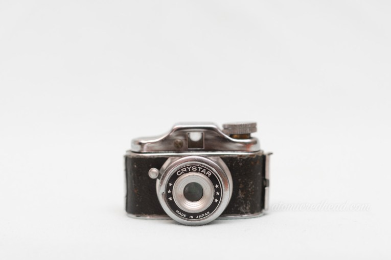 A very small rangefinder style camera of black and silver.