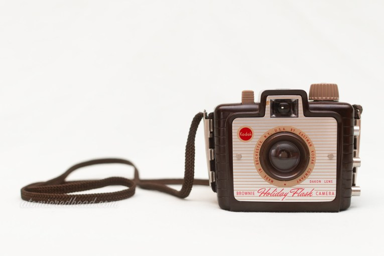 "Kodak Holiday Flash. A small brown square camera with a silver plate on the front. Red script reads ""Holiday Flash"""
