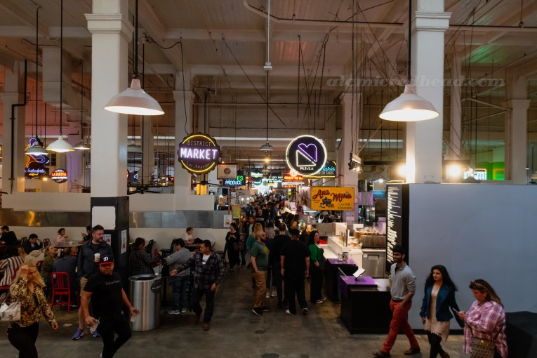 Crowded aisle of Grand Central Market, with various neon signs hanging from the ceiling.