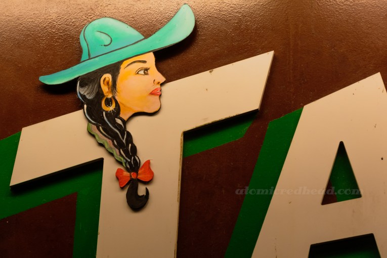Close up of a taco sign, a painting of a woman wearing a turquoise sombrero, long black hair in a braid with a red bow at the end.