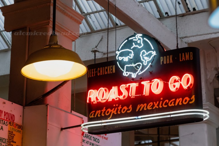 "A neon sign features a cow, chicken, sheep, and pig. Text reads ""Roast to Go Beef-Chicken-Pork-Lamb antojitos mexicanos"""