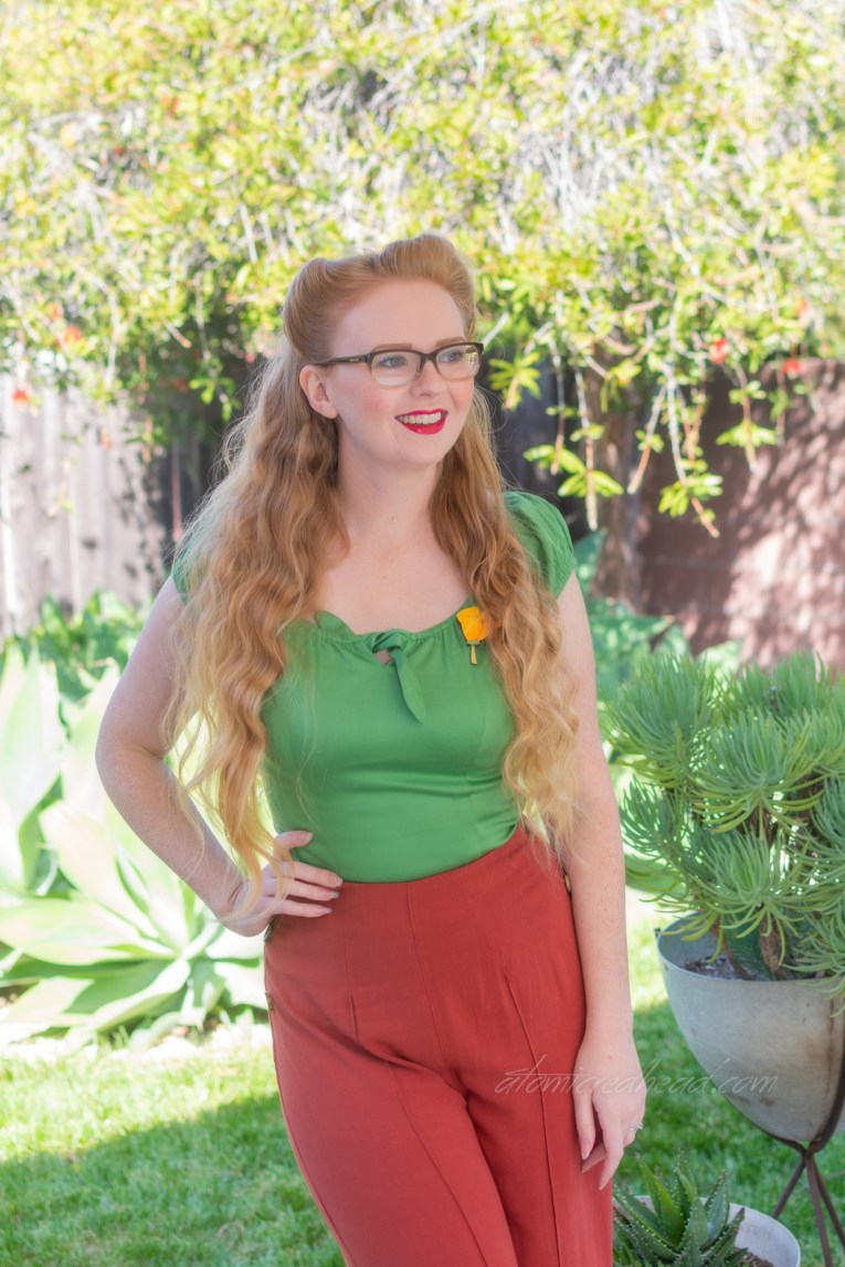 Myself, standing on our patio, with various cacti in the background, wearing a green peasant top with brick red wide leg trousers.