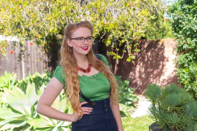 Myself, standing on our patio, with various cacti in the background, wearing a green peasant top with a blue denim skirt with suspenders.