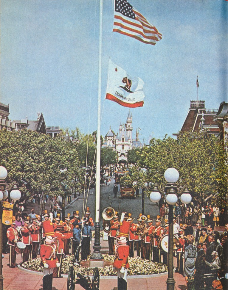 Photograph of the Disneyland Band at the flag pole in Town Square. Here Victorian buildings go into the distance with Sleeping Beauty Castle far off.