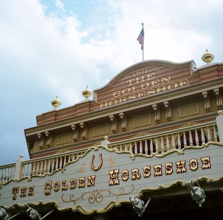 "The Golden Horseshoe, a western style saloon painted a pale orange with a white sign with gold details reading ""The Golden Horseshoe"""