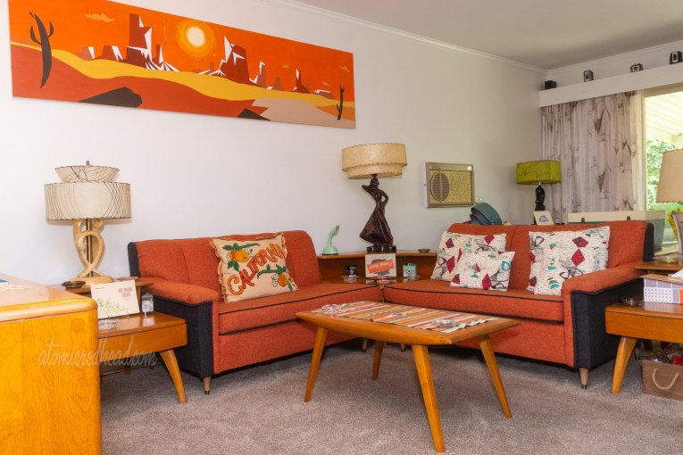 "Two orange and black sofas sit in an L shape. A painting above one sofa features a modern desert landscape. A pillow on one sofa reads ""California"" and features oranges on it. Pillows on the other sofa are abstract modern designs of maroon and teal. A square, step table sits between the two sofas."