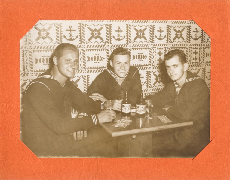 Three sailors sit at a table with wallpaper of a tiki nautical theme behind them.