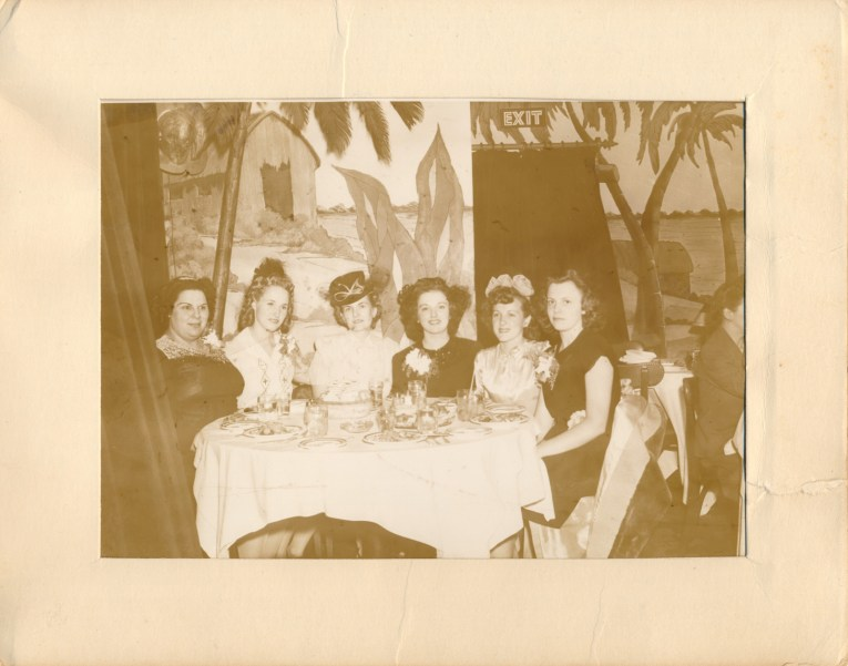 A groupe of six women sit at a table with a tropical mural painted behind them.