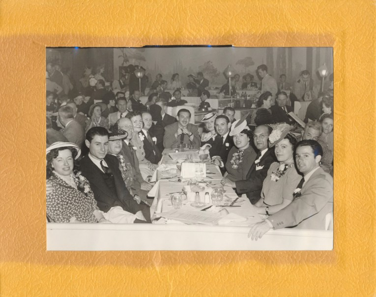A large party with both men and women in suits, the woman wearing hats, and floral corsages, sit at a large table.