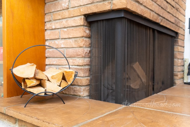 A metal magazine rack sits next to a fireplace with wood on it.