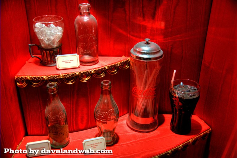 "A flared soda fountain glass, next to a straight clear bottle, embossed with ""Coca Cola"" sit on a shelf above two other bottles, another straight bottle with a longer neck, and a paper diamond label, next to the iconic curved bottle."