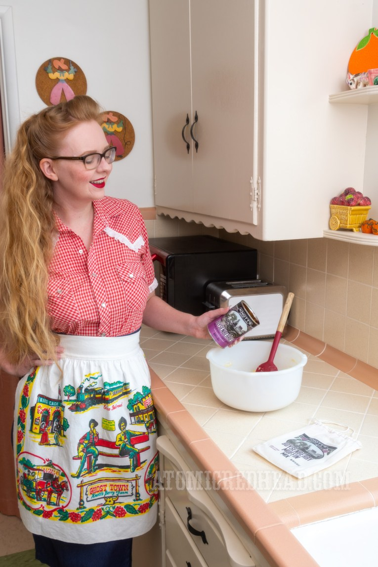 Myself, making the boysenberry muffins, wearing a red and white gingham snap western wear shirt, and an apron featuring images of Knott's Berry Farm on it.