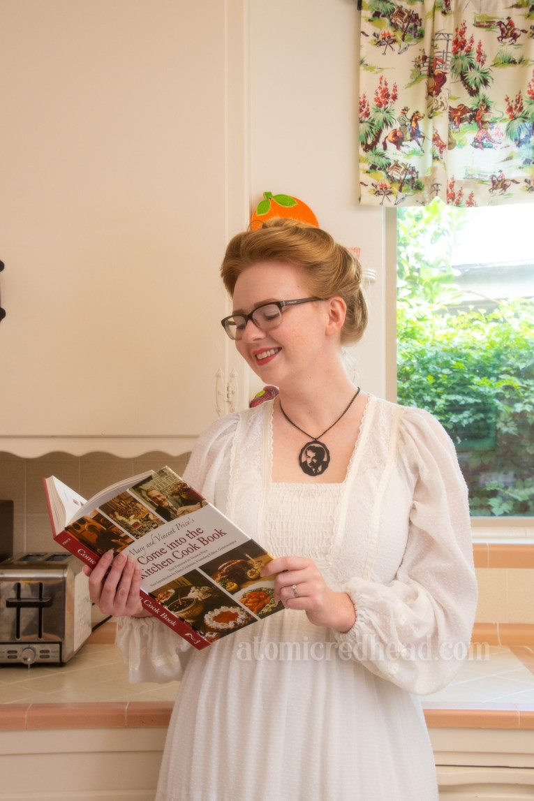 "Myself, wearing a white dress, and a black necklace featuring Vincent Price, holding his book ""Come Into the Kitchen"""