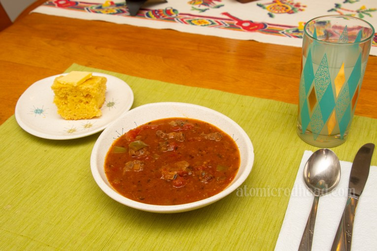 Deep redish-orange gumbo sits in a bowl, a plate with cornbread sits to the left.